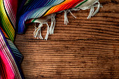 Cinco de mayo fiesta party and indigenous cultures of Mexico concept theme with a Mexican rug called a serape isolated on wood background with copy space