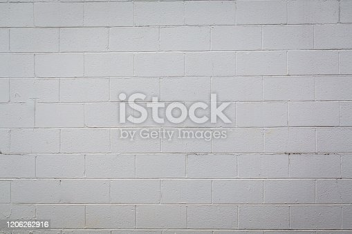 cinder block concrete exterior wall painted white on the outside of a building that has been renovated