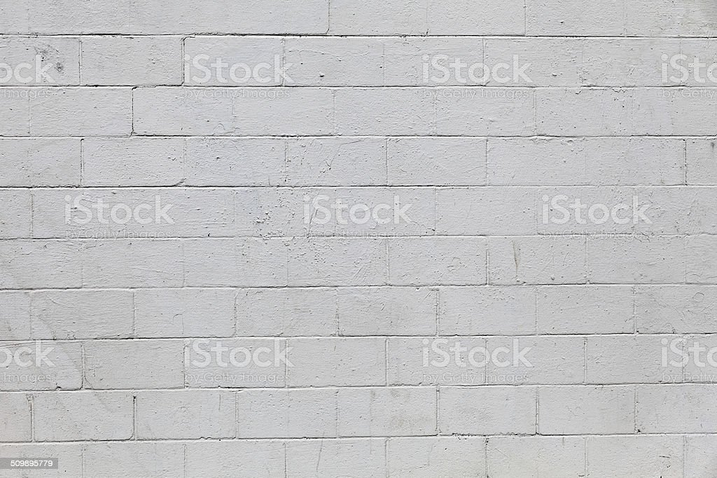 Cinder block wall A cinder block wall painted in white that has been weathered by the outdoors conditions, perfect to use as a background or a composition of any kinds. Backgrounds Stock Photo