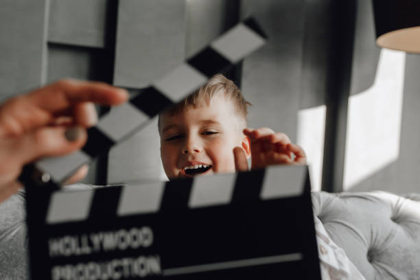 Cinema Clapper Board in Hand Blond Boy on Couch stock photo