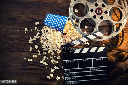 istock Cinema concept of vintage film reel with popcorn 847291668