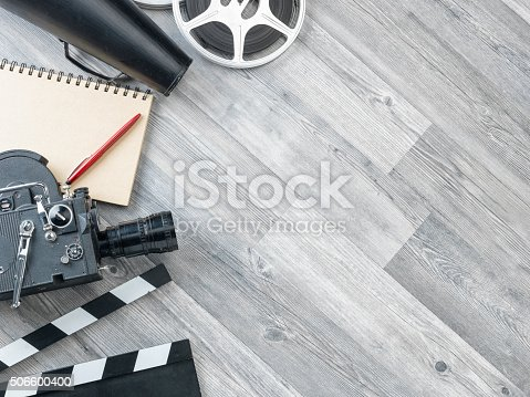Film slate,movie video camera,notepad,pen,megaphone,film reel and film slate on the gray wooden floor.The photo was shot from directly above view point.Copy space on the right side of frame.The notepad is blank.No people are seen in frame.Shot with medium format camera Hasselblad in studio.