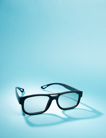 3D movie glasses on blue background.