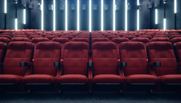 Cinema hall with blank screen and empty seats. Modern design with striking lighting, neon lighting. Audio system on the walls. Cinema hall without people. White screen with copy space, 3D illustration stock photo