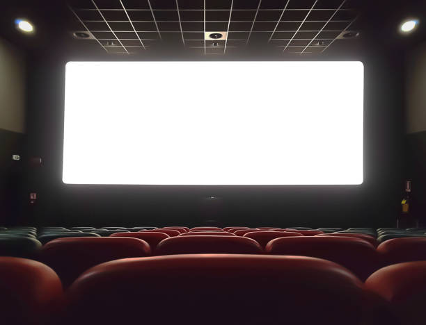 cinema interior of movie theatre with empty red and black seats with copyspace on the screen and glow on edge, concept of recreation stock photo