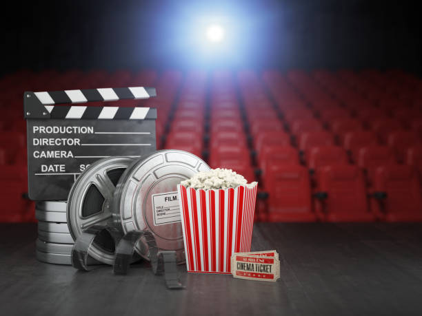 Cinema, movie or home video concept background. Film reels, clapper board  and pop corn in the theater movie cinema screen with empty seats. stock photo