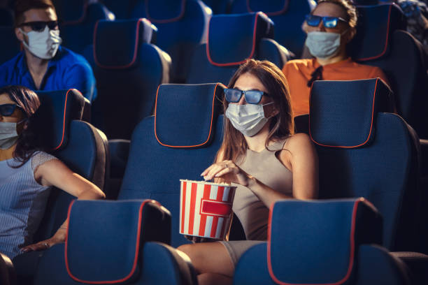 Cinema, movie theatre during quarantine. Coronavirus pandemic safety rules, social distance during movie watching stock photo