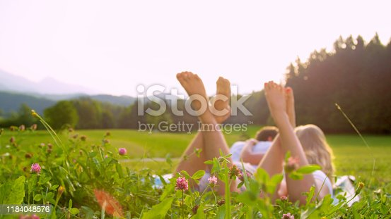 SUN FLARE, CLOSE UP, DOF: Cinematic shot of a young couple lying in the idyllic green countryside and enjoying a relaxing outdoor date in the summer. Spring sunbeams shine on newlyweds and nature