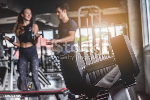 istock Cinematic tone of young attractive fitness woman exercise with dumbbell by trainer in gym. 1135274795