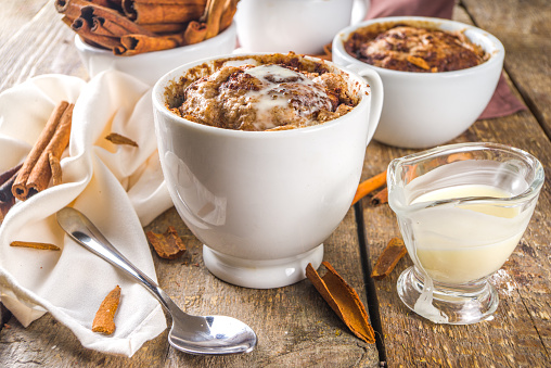 Cinnabon cake in mug. Fast simple microwave dessert idea, background for recipe. Cinnamon roll mugcake, with sugar and cream cheese topping, in different mugs, with cinnamon sticks on wooden background