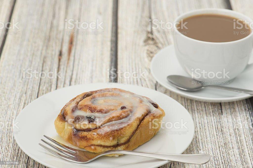 Cinnamon bun on a white plate with coffee stock photo