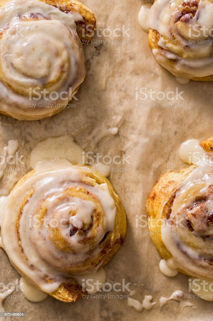 Cinnamon Bun With Icing On Baking Sheet Parchment stock photo
