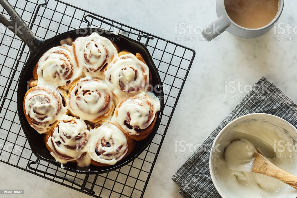 Cinnamon Buns in Cast Iron Skillet with Cream Cheese Icing stock photo