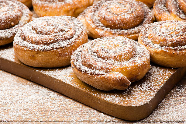Cinnamon buns on the wooden board on the wooden background. stock photo