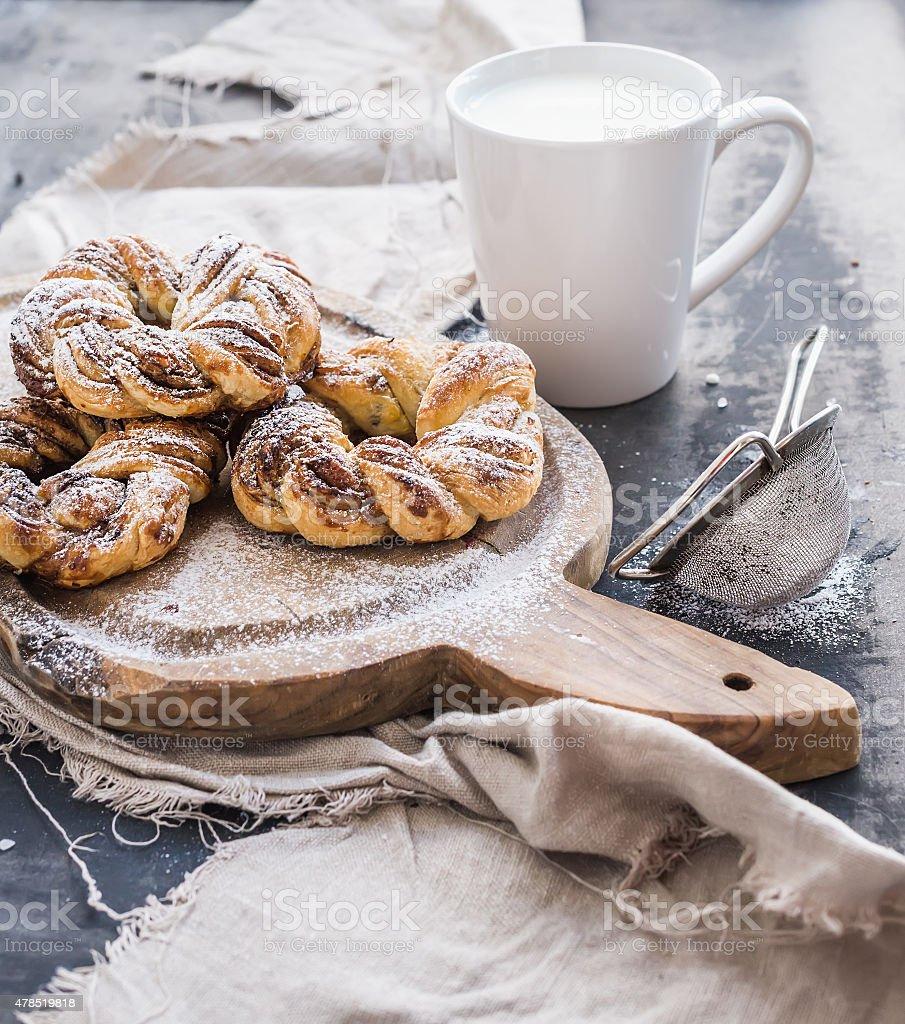 Cinnamon buns with sugar powder on rustic wooden board, mug stock photo