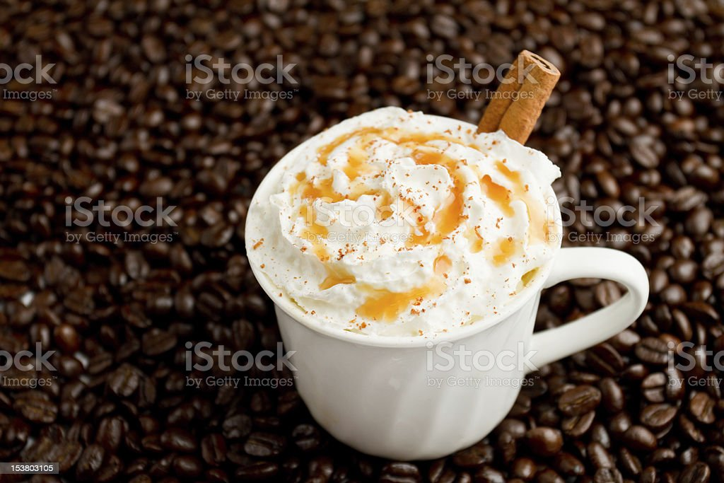Cinnamon cappuccino with a fresh stick of cinnamon arranged on a bed...