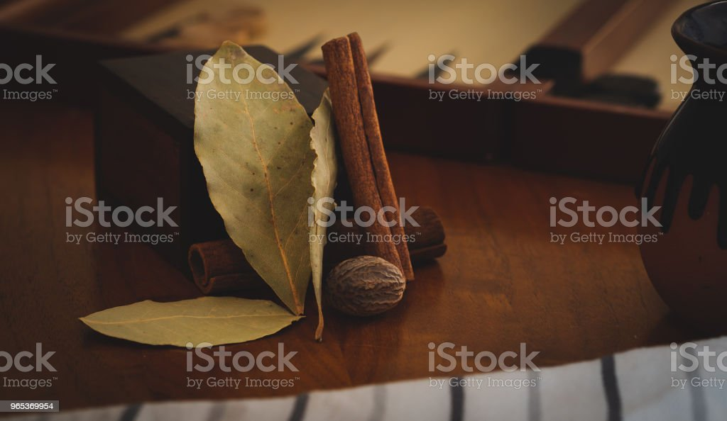 Cinnamon, nutmeg and bay leaves resting on a wooden table zbiór zdjęć royalty-free