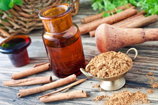 cinnamon oil and sticks with powder - oli, aromi e spezie foto e immagini stock