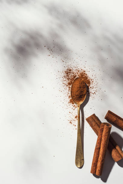 Cinnamon powder and rolls Cinnamon powder in a spoon and cinnamon rolls pn white background. Dried herbs shot from directly above. anti inflammatory stock pictures, royalty-free photos & images