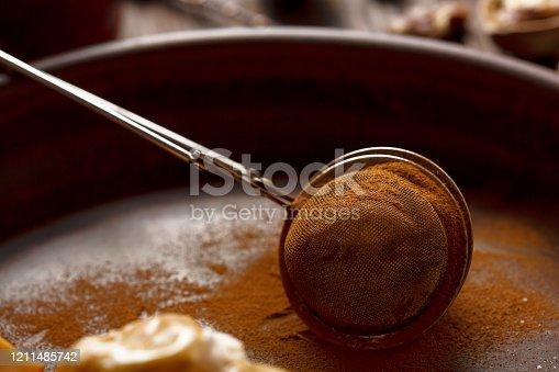 Cinnamon powder in a culinary strainer. Baking ingredient
