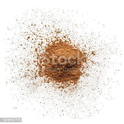 Top view of cinnamon powder heap isolated on white background. Predominant colors are brown and white. High key DSRL studio photo taken with Canon EOS 5D Mk II and Canon EF 100mm f/2.8L Macro IS USM.
