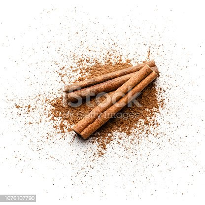 Top view of cinnamon powder heap with two cinnamon sticks isolated on white background. Predominant colors are brown and white. High key DSRL studio photo taken with Canon EOS 5D Mk II and Canon EF 100mm f/2.8L Macro IS USM.