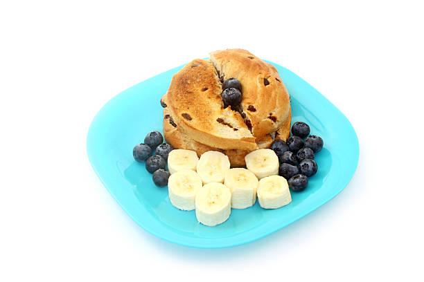 Cinnamon Raisin Bagel With Bananas and Blueberries stock photo