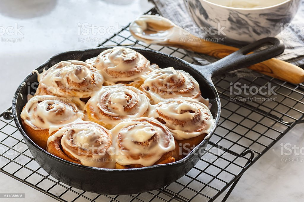 Cinnamon Rolls in Cast Iron Skillet with Cream Cheese Icing stock photo