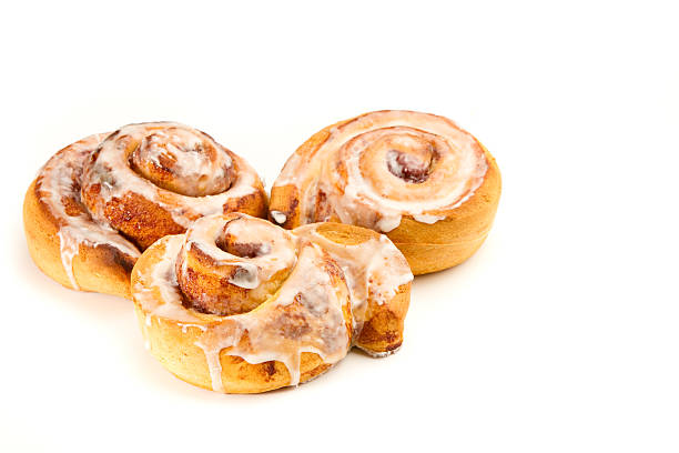 Cinnamon Rolls This is a photo of a tasty cinnamon roll coated in icing. Shot with a shallow depth of field on an isolated white background. sweet bun stock pictures, royalty-free photos & images