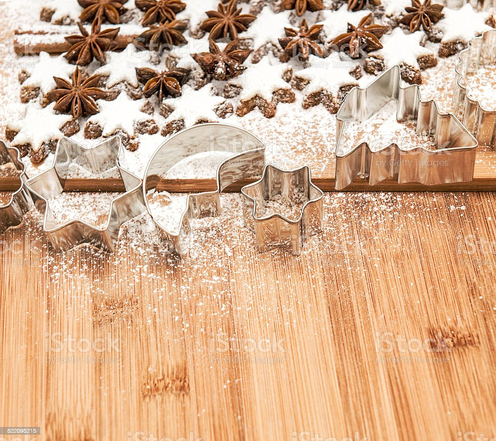 cinnamon stars and cookies cutters on wooden background stock photo