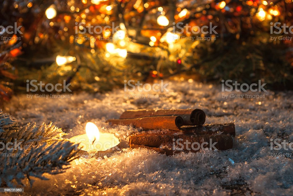 Cinnamon sticks and candle in the snow. foto royalty-free