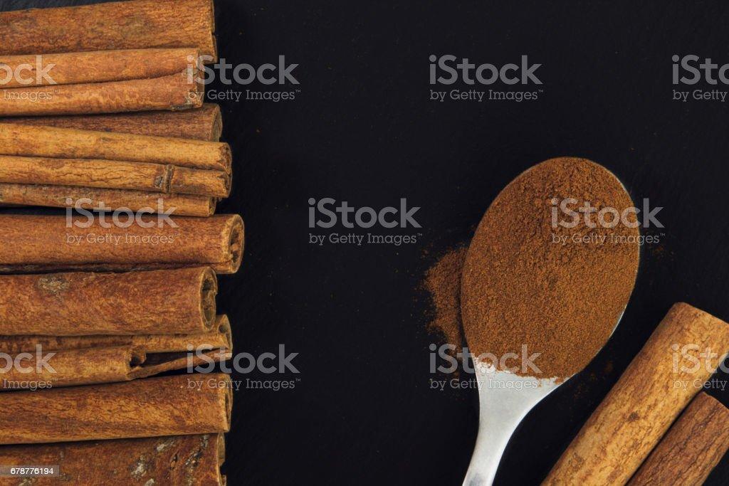 Tarçın ve siyah arduvaz plaka üzerinde çay kaşığı toz tarçın royalty-free stock photo