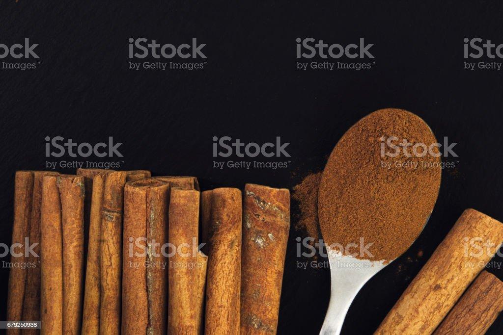 Cinnamon sticks and cinnamon powder in the tea spoon on black slate plate foto de stock royalty-free