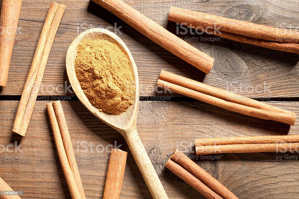 Cinnamon sticks and powder on old table stock photo