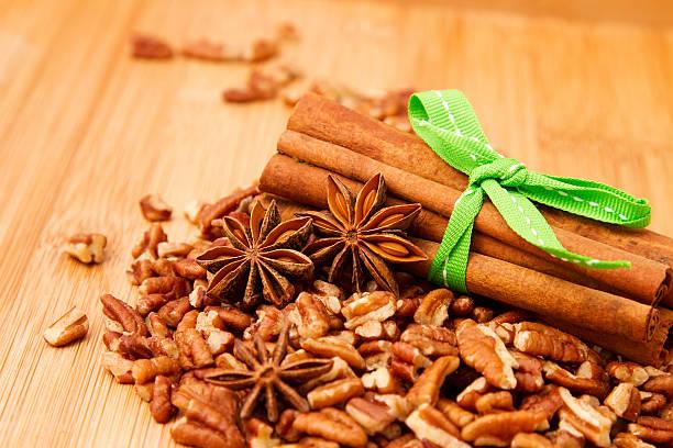 cinnamon sticks, anis und pekanfarbene nüssen auf hölzernen tischplatte - zimt pekannüsse stock-fotos und bilder