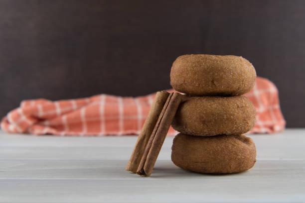zimtstangen gelehnt donuts - hausgemachte gebackene donuts stock-fotos und bilder
