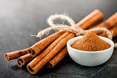 Cinnamons dried sticks on dark stone table. Cinnamon ginger powder in white bowl on black board.