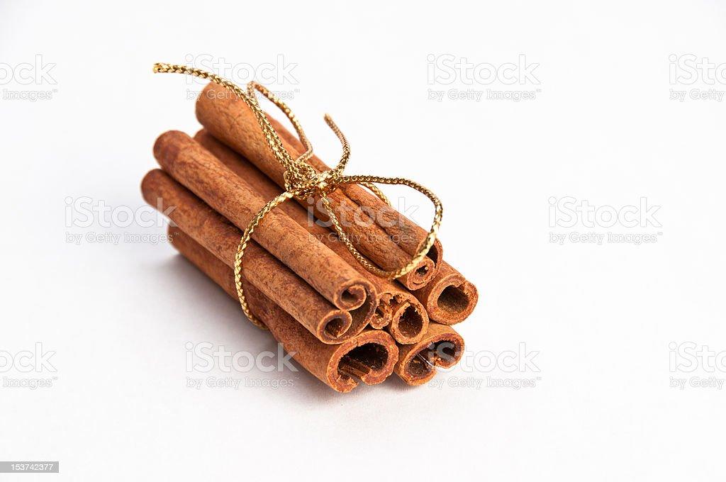 Cinnamon sticks with gold ribbon on white background stock photo
