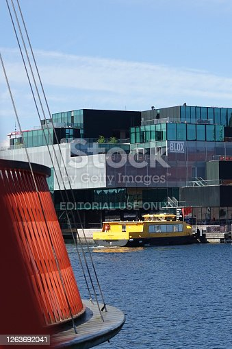 The BLOX building seen through the Circle Bridge spanning over the Christianshavn Canal on a sunny day in Copenhagen, Denmark. The Circle Bridge (Danish: Cirkelbroen) is a pedestrian bridge and consists of five round decks with masts of different heights. The bridge was designed by Olafur Eliasson and opened in 2015