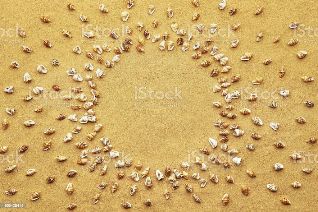 Circle frame made of tiny sea shells on beach sand background. zbiór zdjęć royalty-free