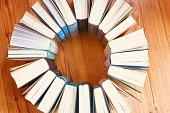 Circle of books on parquet floor