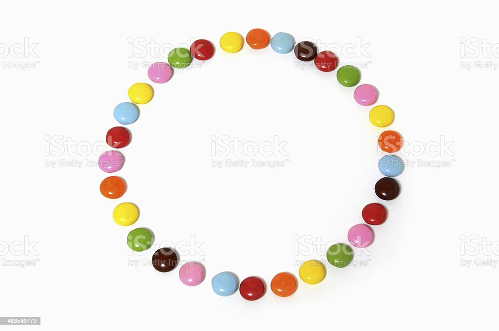 circle of colorful chocolate candies spread on white background stock photo