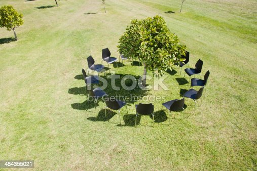 istock Circle of office chairs around tree in field 484355021