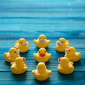 istock Circle of yellow rubber ducks wearing surgical face masks around a single yellow rubber duck who is not wearing a surgical face mask. Scene set on a wooden turquoise colored background, conceptually representing water. 1221595094