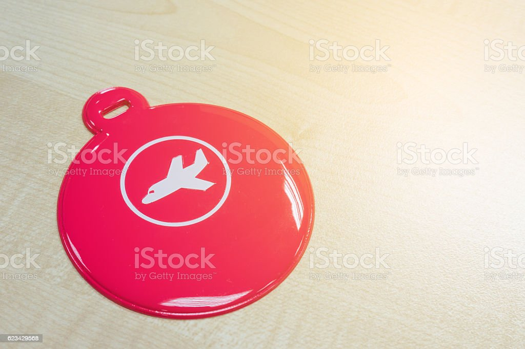 Circle pink luggage tag on wooden table stock photo