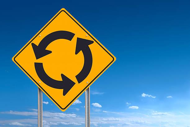 panneau indicateur circle rond-point sur ciel bleu en arrière-plan - rond point carrefour photos et images de collection