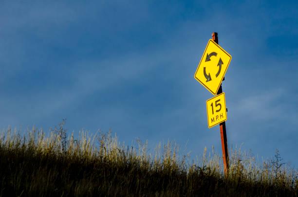kreis-kreisverkehr-straßenschild über blauem himmel mit einem veröffentlichten geschwindigkeitslimit von 15 mph - sich im kreis drehen stock-fotos und bilder
