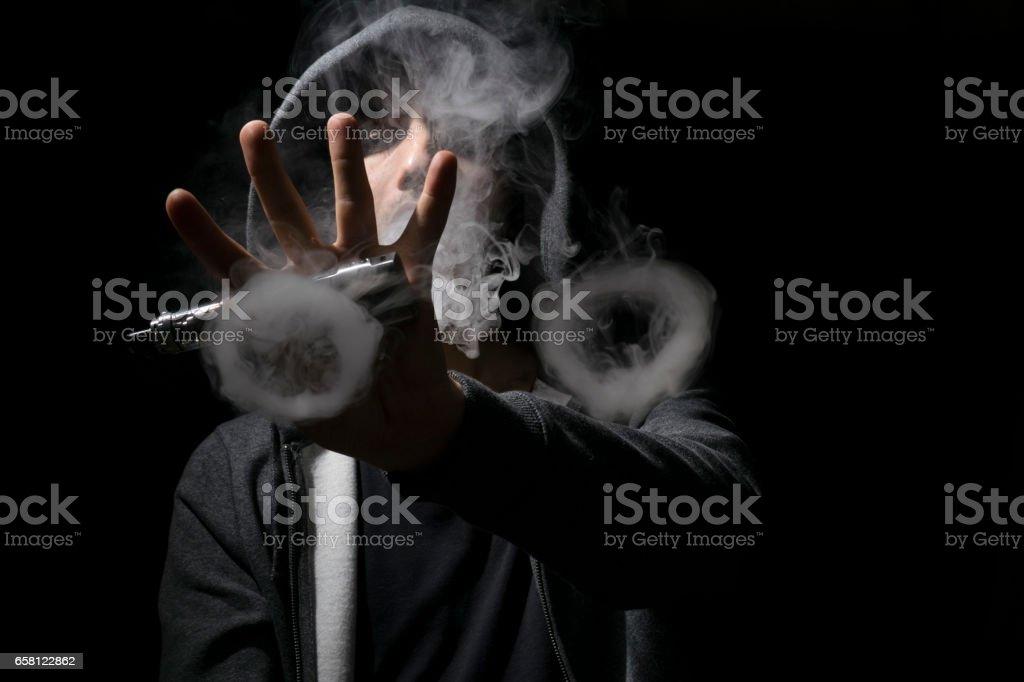 Young man doing vaping tricks circles.