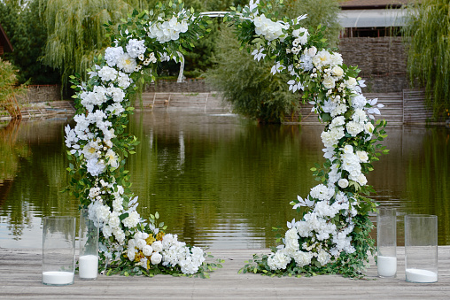 Circle wedding arch decorated with white flowers and greenery outdoors, copy space. Wedding setting. Floral composition
