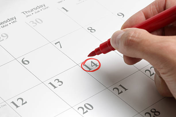 a circled date on a large calendar in red ink - calendar date stock photos and pictures